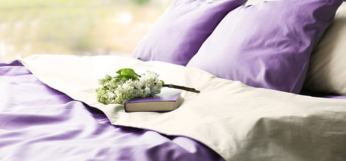 neatly made bed with purple sheets and pillows in front of a window overlooking a green meadow